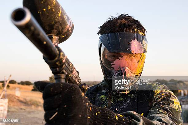 paintball player with paintball mask and paintball gun stained with paint - paintball foto e immagini stock