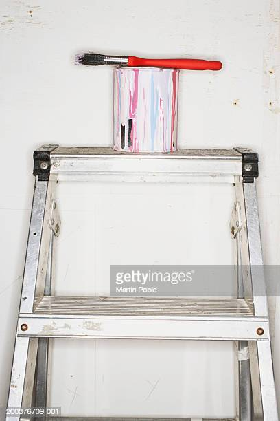 paintbrush balanced on open paint can on stepladder - step ladder stock photos and pictures
