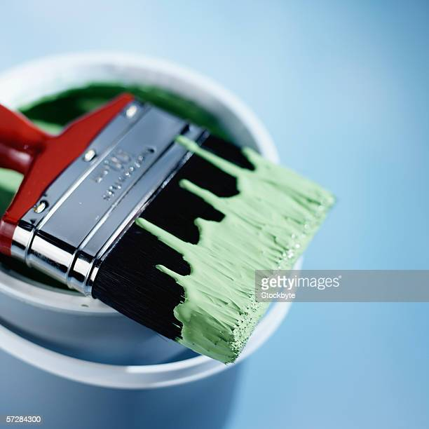 Paintbrush dipped in green paint resting on tin of paint