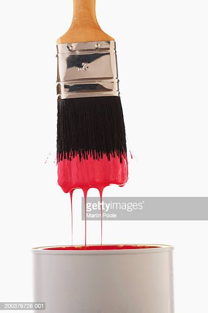 paintbrush dripping red paint into paint can, close-up - paintbrush stock pictures, royalty-free photos & images