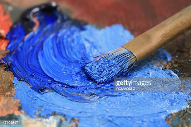 Paintbrush with blue oil paint on a classical palette