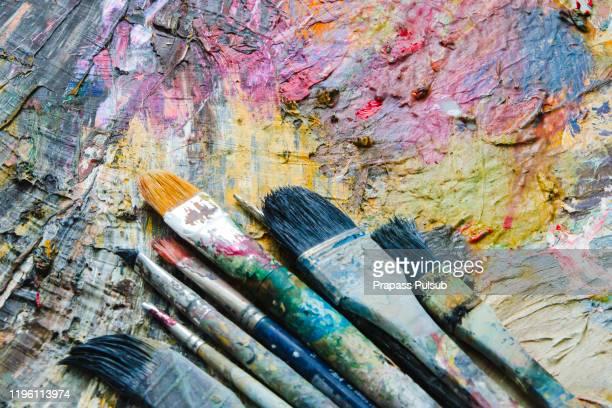 paintbrushes closeup, artist palette and multicolor paint stains - malerleinwand stock-fotos und bilder