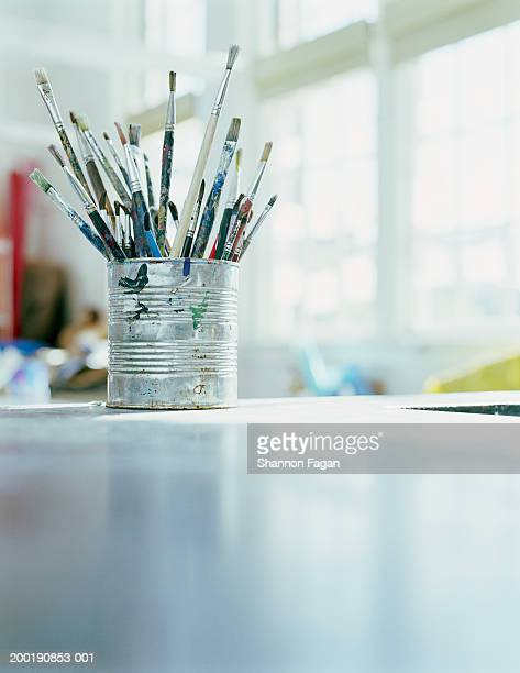 Paintbrushes in tin can on desk in classroom, close-up