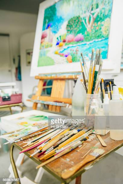Paintbrushes, palette and easel with painting in studio
