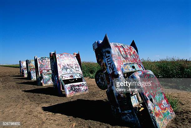 Painted and graffitied Cadillacs emerge from the ground at Stanley Marshall's Cadillac Ranch | Located in Amarillo