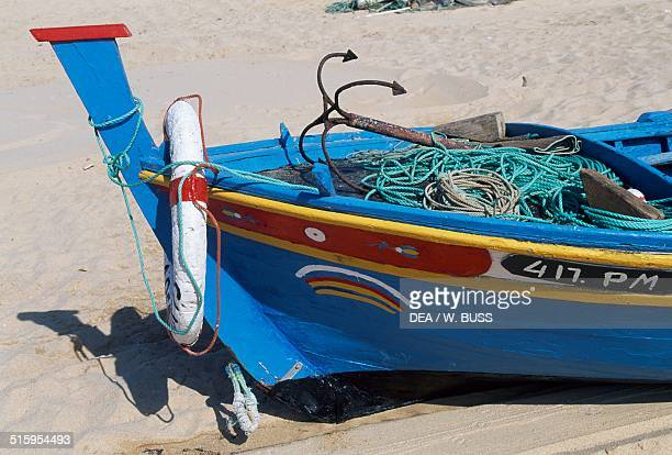 Painted bow of a fishing boat docked on the beach Armacao de Pera Algarve Portugal