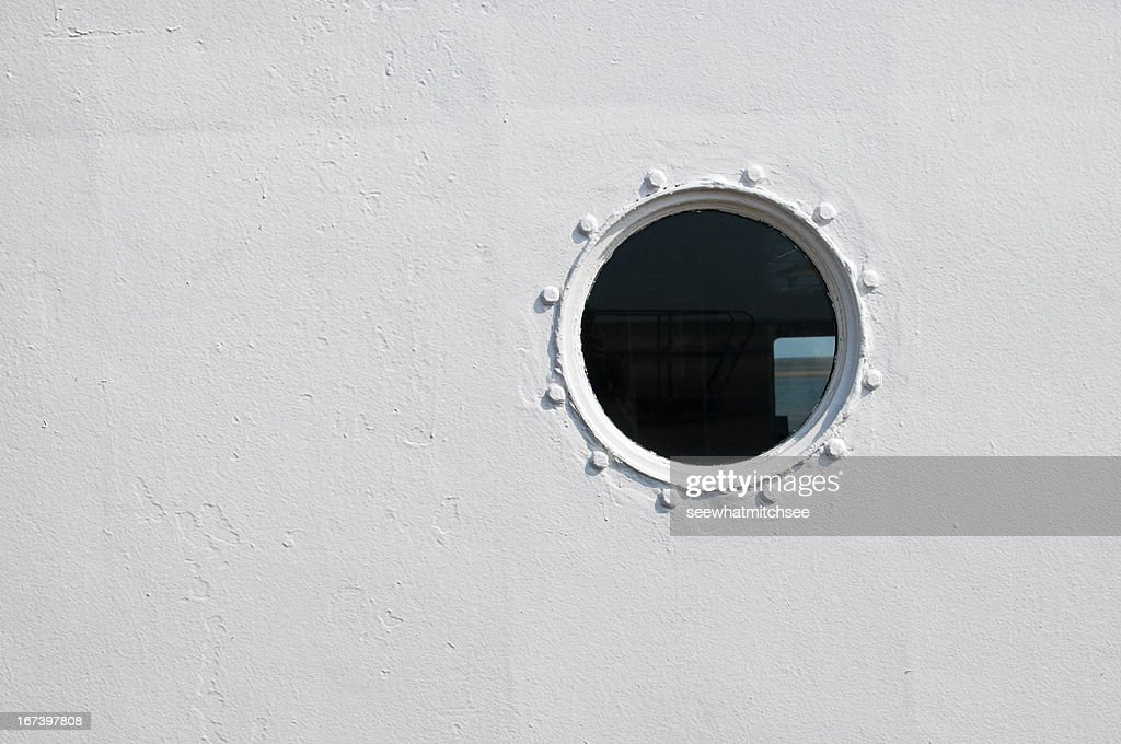 Painted brass porthole on the side of a ship : Stock Photo