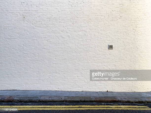 painted bricks wall with sidewalk and street in london - muur stockfoto's en -beelden