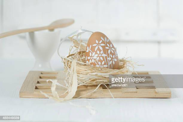 Painted easter egg in straw neston white background