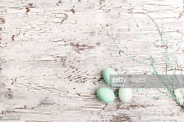 Painted Easter eggs over white wooden background