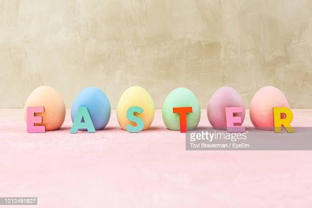 painted easter eggs with easter text letters and copy space - happy easter text stock pictures, royalty-free photos & images