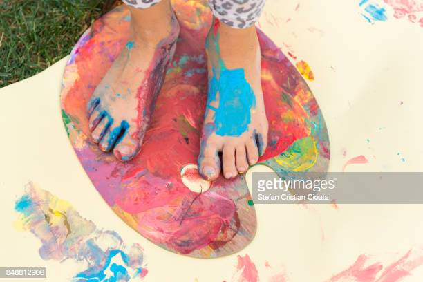 Painted feet on a colorful painting palette