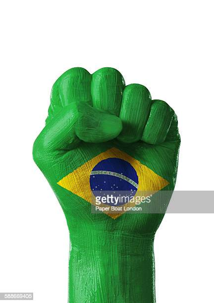 painted flag of brazil on a hand in white studio