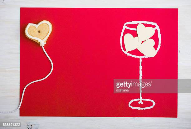 Painted glass of wine and three hearts in the glass with heart shaped cookie