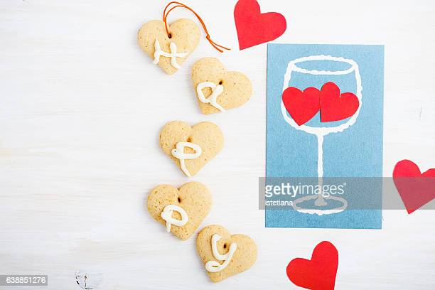 Painted glass of wine and two hearts in the glass with heart shaped cookie