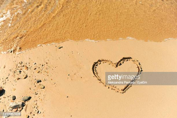 painted heart on clean sand of beach and a wave of clear transparent water rolls, not glossy image - sand stock pictures, royalty-free photos & images
