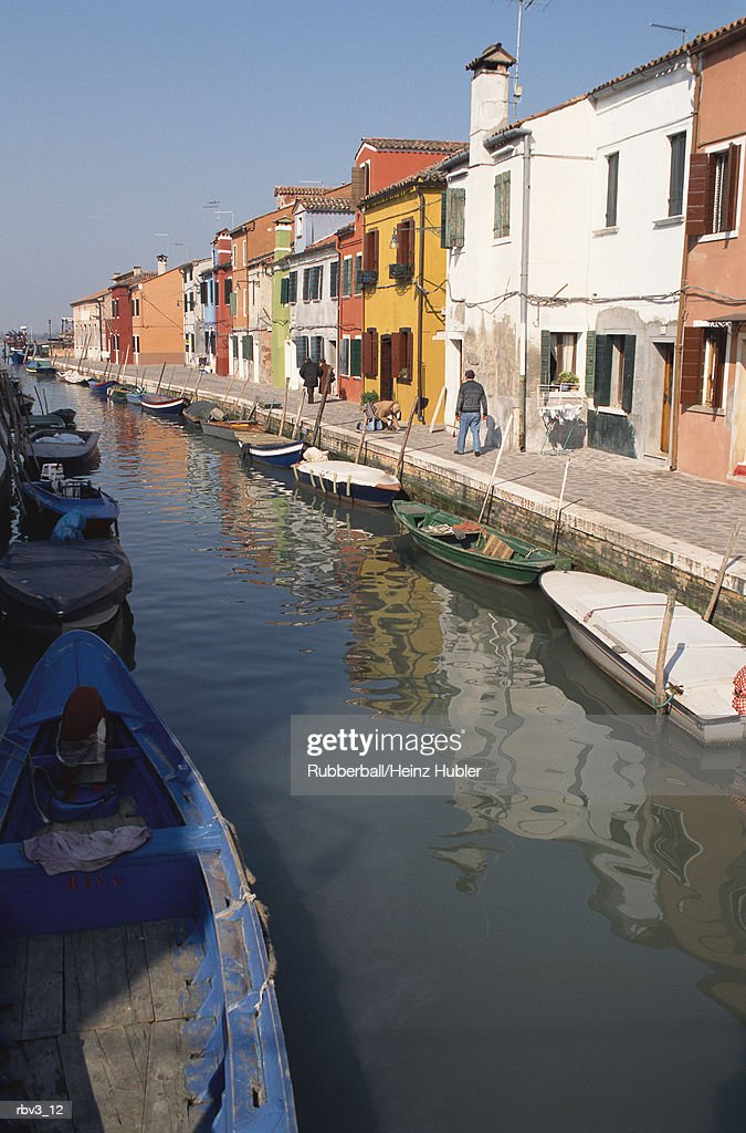 painted houses and boats line the edge of a reflective canal in Europe under a clear blue sky : Bildbanksbilder