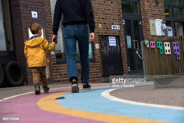 Painted lines are seen in a school playground as a man walks with a child into a polling station at Jessop Primary School in the constituency of...