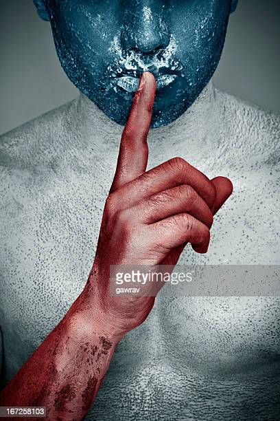 Painted man with naked body putting index finger on lips