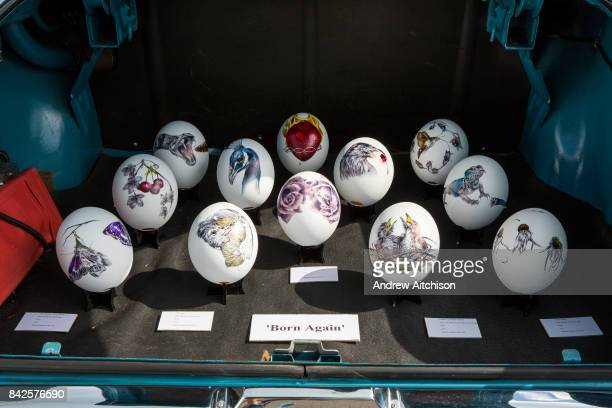 Painted ostrich eggs in the boot of a Vauxhall car by artist Kate Knight on sale at the 2017 Art Car Boot Fair Folkestone Kent
