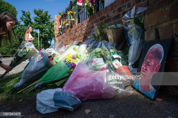A painted portrait is seen among the flowers as students pay their respects to the murdered school teacher James Furlong outside The Holt School on...