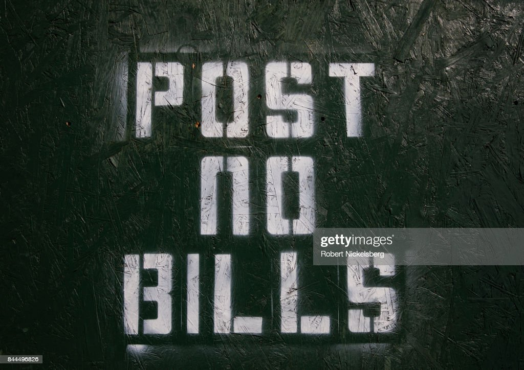 a painted sign around a construction site reads post no bills in