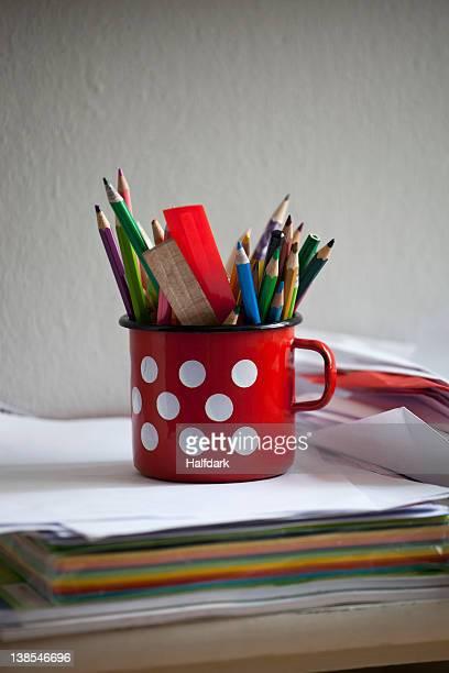 A painted tin mug full of colored pencils