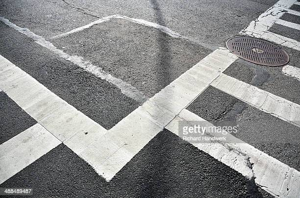 Painted white traffic crossing lines on street