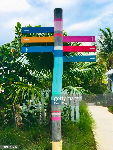 painted wooden post with directional arrows - nassau stock pictures, royalty-free photos & images