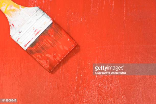 painted wooden surface. Red color. Varnishing natural wood with paint brush.