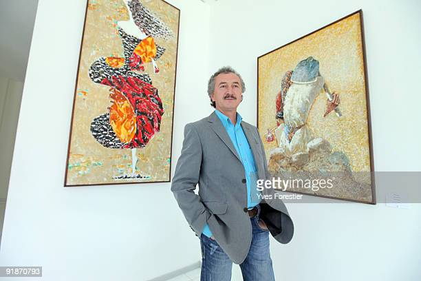 Painter Akmal Nur poses with his works during the Akmal Nur Exhibition opening at The Center of National Arts on October 13 2009 in Tashkent...