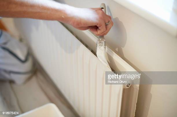 Painter and decorator at work painting radiator