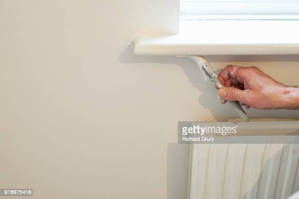 Painter and decorator at work painting windowsill