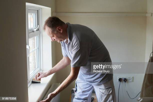 Painter and decorator at work sweeping dust from windowsill