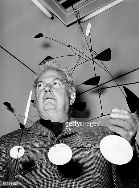US painter and sculptor Alexander Calder displays 13 March 1955 one of his mobiles in a gallery in Rome Calder first studied mechanical engineering...