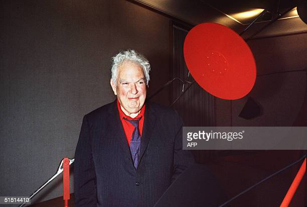 US painter and sculptor Alexander Calder smiles to the photographer 10 October 1968 in front of one of his mobiles during a preview at a Paris art...