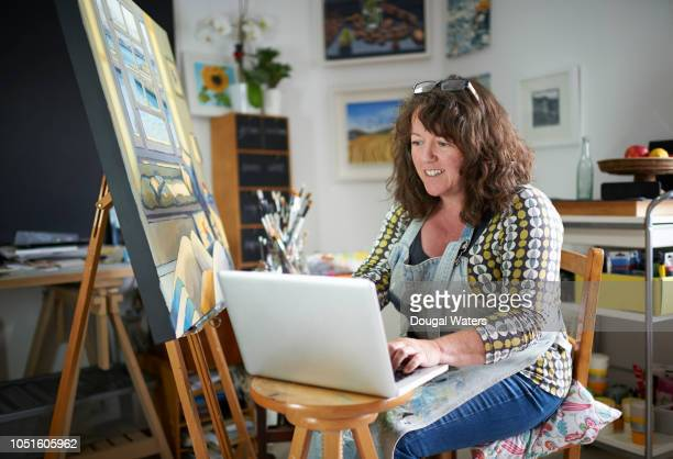 Painter artist in studio using laptop.