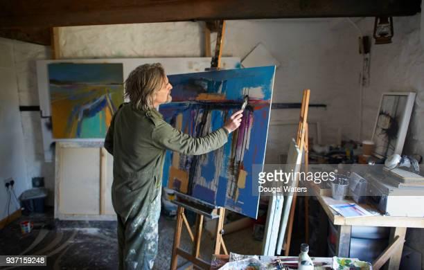 Painter artsit working on painting in studio.