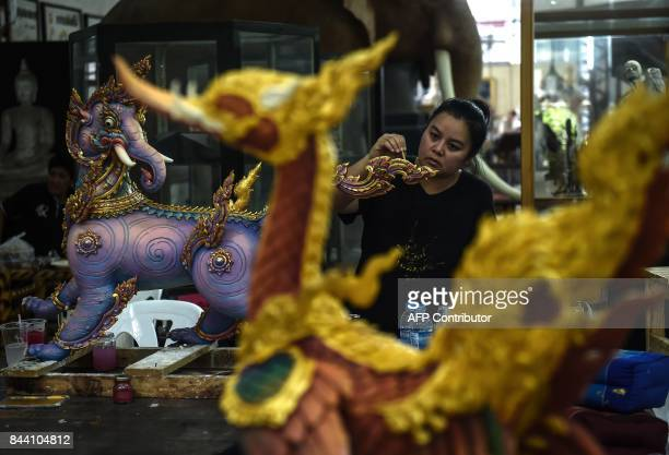 A painter from the Fine Arts Department works on one of the statues to decorate the cremation site for the late Thai king Bhumibol Adulyadej at...