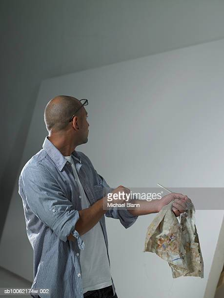 Painter holding brush, looking at blank canvas