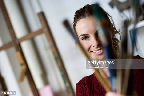Painter holding bunch of brushes