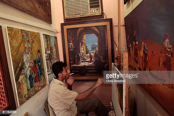 Painter Hussein al Musawi smokes as he works in his studio in the alAsfar artist's district May 20 2008 in Baghdad Iraq AlAsfar is Baghdad's main...