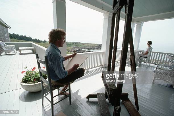 Painter Jamie Wyeth son of painter Andrew Wyeth works on a drawing while sitting in a chair on a white verandah Monhegan Island Maine