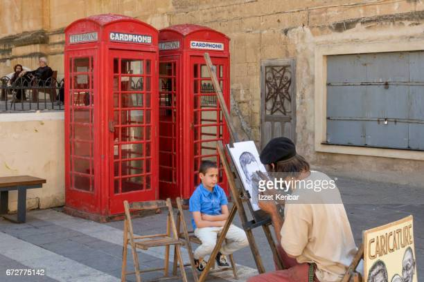 Painter making drawing of a child, Valletta, Malta