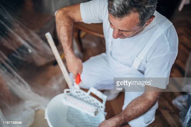 painter man at work with a paint roller and ladder - artist stock pictures, royalty-free photos & images