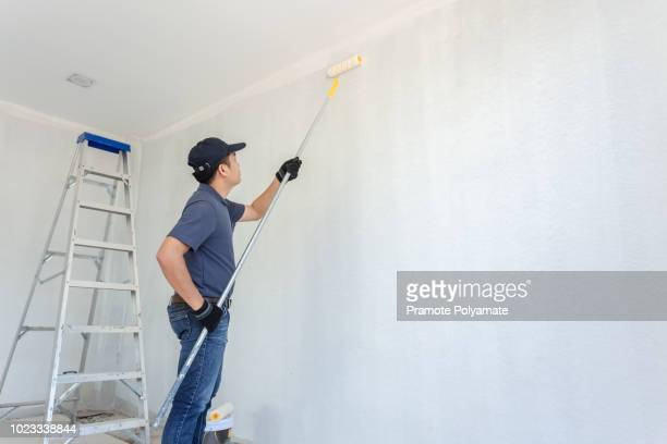 painter man at work with a paint roller on the wall. - whitewashed stock photos and pictures