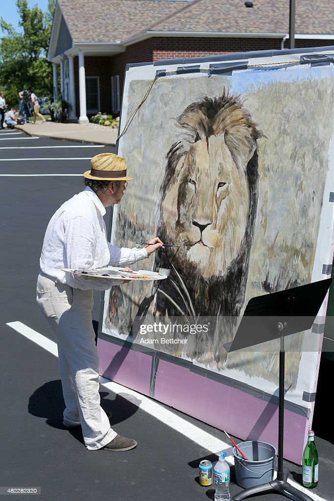 Painter Mark Balma paints a portrait of Cecil the lion to donate to anti-poaching efforts in the parking lot of Dr. Walter Palmer's dental clinic on July 29, 2015 in Bloomington, Minnesota. According to reports, the 13-year-old lion was lured out of a national park in Zimbabwe and killed by Dr. Palmer, who had paid $50,000 for the hunt.