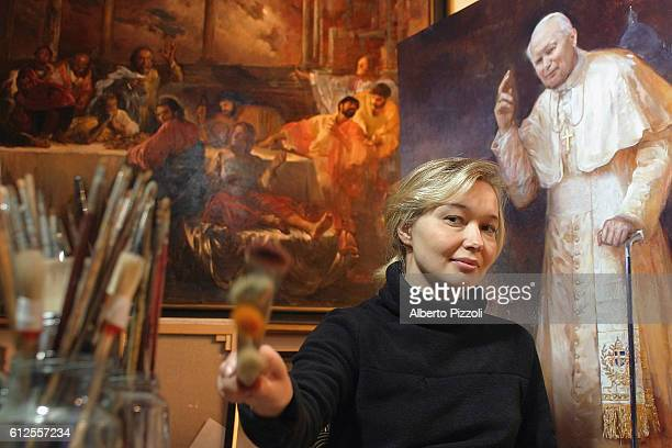 Painter Natalia Tsarkova sits in her central Rome workshop between a copy of one of her portraits of Pope John Paul II and one of her own paintings...