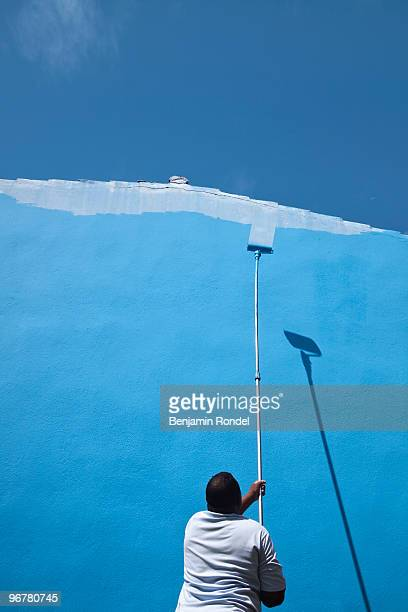 Painter painting an exterior wall with blue paint.