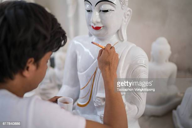 painter painting color on buddha marble statue sculpture
